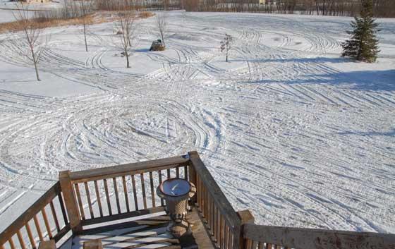 Snowmobile tracks in the yard