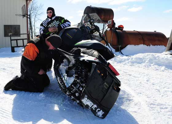 Arctic Cat's Roger Skime and Brian Dick adjust a sled suspension